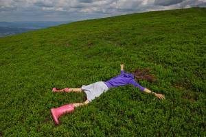 Girl lying facedown on the green bluberry field in the Carpatian mountain